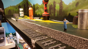 Started building the background team track a few days ago.  Glued on first stone wall against the platform this morning. Further away there will be an ore loading ramp for the ore wagons. For this the first sleepers looked a bit to much up-scaled peco....